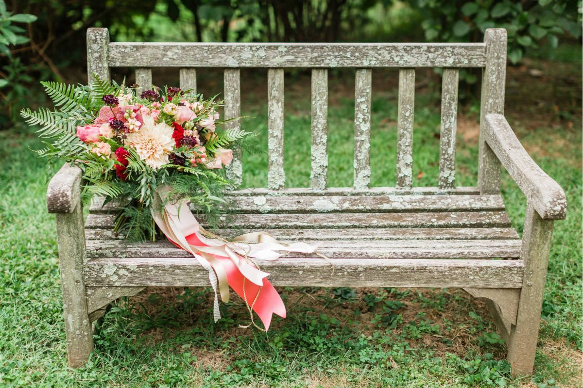 weathered wooden bench with a colorful bridal bouquet