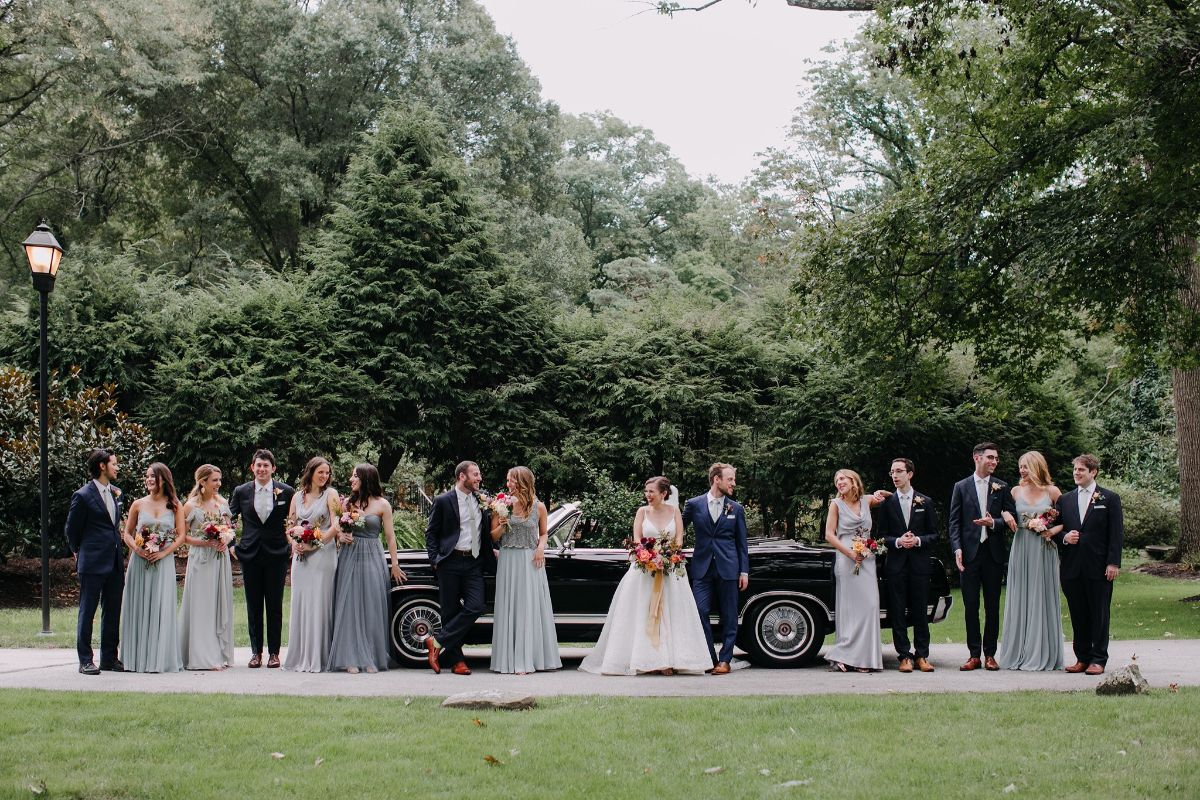 bridal party in front of a luxury convertible